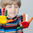 Five year old boy with hands painted in colorful paints ready fo — Stock Photo #22728539