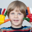 Five year old boy with hands painted in colorful paints ready fo — Stock Photo