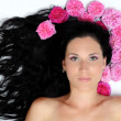 Beautiful girl lies in the hair roses — Stock Photo