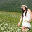 A pregnant girl in a field of flowers - Stock Photo