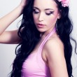 Beautiful girl with pink flowers in her hair - Stock Photo