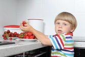 Boy takes strawberries from the saucer in the kitchen — Stock Photo