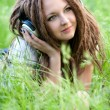 Stock Photo: Pretty girl with dreads listening to music