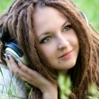 Pretty girl with dreads listening to music — Stock Photo #22766498