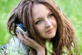 Pretty girl with dreads listening to music — Stock Photo
