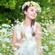 Beautiful woman enjoying daisy field, pretty girl relaxing outdoor, having fun, holding plant, happy young lady and spring green nature, harmony concept — Stock Photo