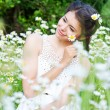 Beautiful woman enjoying daisy field, pretty girl relaxing outdoor, having fun, holding plant, happy young lady and spring green nature, harmony concept — ストック写真