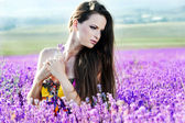 Beautiful girl on the lavender field. Young woman collects lavender — Stock Photo