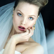 Beautiful bride brunette girl in white wedding dress with hairstyle and bright makeup looks in the mirror — Stock Photo #29953481