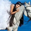 Foto Stock: Beautiful bride with the horse on the sea shore. Horsewoman