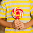 Hands holding spiral lollipop — Stock Photo