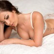 Beautiful woman resting on the bed — Stock Photo #37315287