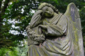 Sad angel statue on old cemetery — Stock Photo