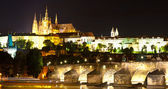 Panoramic night view to Lesser Town, Prague castle, St. Nicholas church and Charles bridge — Stock Photo
