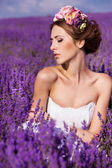 Beautiful Bride in wedding day in lavender field. Newlywed woman in lavender flowers. Young woman in wedding dress outdoors. — Stok fotoğraf
