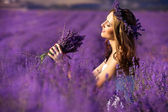 Beautiful Bride in wedding day in lavender field. Newlywed woman in lavender flowers. Young woman in wedding dress outdoors. — Foto Stock