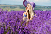 Beautiful girl in violet hat on the lavender field. Young woman with long hair collects lavender — Stock Photo