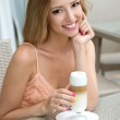 Pretty young woman sitting in a cafe with a cup of coffee latte — Stock Photo #50979207