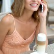 Pretty young woman sitting in a cafe with a cup of coffee latte and  talking on the phone at a cafe — Stock Photo #50979227