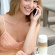 Pretty young woman sitting in a cafe with a cup of coffee latte and talking on the phone at a cafe — Stock Photo