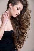 Uzun kıvırcık saçlı genç güzel kadın — Stok fotoğraf