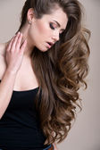 Young beautiful woman with long curly hair — Stockfoto