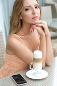Pretty young woman sitting in a cafe with a cup of coffee latte — Stock Photo
