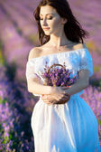 Beautiful girl on the lavender field. Young woman with long hair collects lavender — 图库照片