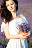 Beautiful girl on the lavender field. Young woman with long hair collects lavender — Stock Photo