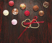 Colorful pralines candies with two hearts and ribbon wooden floor — Stok fotoğraf