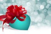 Turquoise blue heart with red bow on bokeh background — Stock Photo
