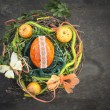 Orange easter egg in bird's nest with decoration on wooden table — Stock Photo