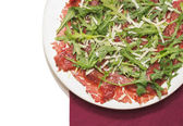 Carpaccio of beef with rucola and Parmesan on red napkin — Stock Photo