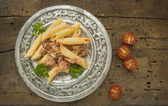 Penne pasta with tuna sauce in silver plate on old wood — Stock Photo