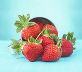 Handful of strawberries on blue background — Stock Photo