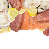 Fresh fish and seafood mix, tuna, salmon, shrimp, Scallops, ingredients for sushi with lemon, isolated — Stock Photo