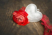 Silver heart and red rose on old wooden table — Stock Photo