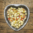 Chopped apples with sugar and sesame seeds in baking dish Heart shaped on old wooden table, top view — Stock Photo
