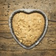 Sponge cake heart shaped in baking dish against background of wooden table , top view — Stock Photo