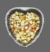 Pommes hachées avec graines de sésame et de sucre dans la cuisson plat coeur en forme, isolé sur gris — Photo