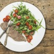 Beef with rocket salad and tomatoes on old wood table, dietetic food — Stock Photo #40181783