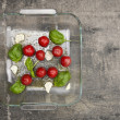 Tomatoes with basil and garlic in glass basin on old wood, preparation for roasting, top view — Stock Photo