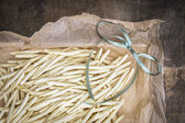 Homemade noodles, fileja, with green bow, packing in wrinkled paper, close up — Stock Photo