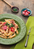 Penne pasta with tuna and tomatoes sauce in green plate, rustic — Stock Photo