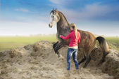 Woman in red jacket and rising arabian horse on background of sand and fields — Zdjęcie stockowe