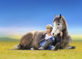 Girl with grey Arabian horse lie on yellow field — Stock Photo