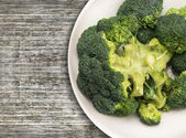 Broccoli head  in white  bowl on old wooden table,clouse up — Stock Photo
