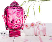 White towel with flowers and  head of glass Buddha, spa — Stok fotoğraf