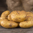 Fresh potatoes on dark old wooden background — Stock Photo #44799853