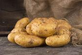 Fresh potatoes on  dark  old wooden background — Stock Photo